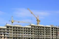 Bouwkranen en een huiskader op een blauwe hemel Stock Afbeelding