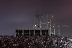 Bouwkranen op een de winternacht Stock Foto