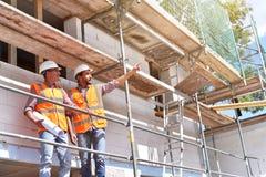 Bouwmanager en architect op plaats tijdens de bouw van een huis - planning en controle op plaats - groepswerk royalty-vrije stock fotografie