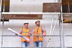 Bouwmanager en architect op plaats tijdens de bouw van een huis - planning en controle op plaats - groepswerk stock afbeelding