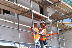 Bouwmanager en architect op plaats tijdens de bouw van een huis - planning en controle op plaats - groepswerk stock afbeeldingen