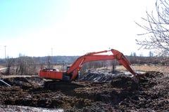Bouwmateriaal die een gat graven oranje graafwerktuig die in de grond lopen de lente, zonnige dag royalty-vrije stock fotografie