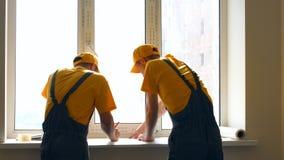Bouwmedewerkers die werkplan bespreken stock fotografie