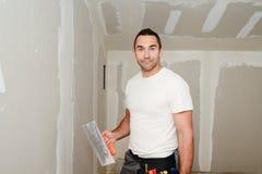 Bouwnijverheidsarbeider met hulpmiddelen die muren pleisteren en huis in bouwwerf vernieuwen Royalty-vrije Stock Fotografie