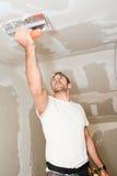 Bouwnijverheidsarbeider met hulpmiddelen die muren pleisteren en huis in bouwwerf vernieuwen Royalty-vrije Stock Afbeelding