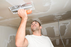 Bouwnijverheidsarbeider met hulpmiddelen die muren pleisteren en huis in bouwwerf vernieuwen Stock Foto's
