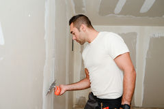 Bouwnijverheidsarbeider met hulpmiddelen die muren pleisteren en huis in bouwwerf vernieuwen Royalty-vrije Stock Foto's