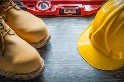 Bouwniveau de laarzen van het de veiligheidsleer van de de bouwhelm op woode Stock Afbeelding