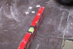 Bouwniveau die thuis de kleefstof van de tegelvloer betegelen stock afbeelding