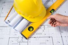 Bouwplannen met helm en tekeningshulpmiddelen op blauwdrukken Stock Foto's
