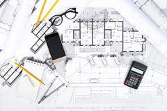 Bouwplannen met smartphone, calculator en tekeningshulpmiddelen Stock Afbeeldingen