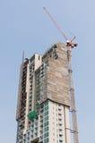 Bouwterrein met high-rise blok in aanbouw in een stedelijk die milieu door een grote industriële kraan wordt overheerst royalty-vrije stock foto's