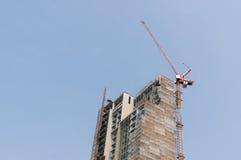 Bouwterrein met high-rise blok in aanbouw in een stedelijk die milieu door een grote industriële kraan wordt overheerst stock foto