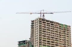Bouwterrein met high-rise blok in aanbouw in een stedelijk die milieu door een grote industriële kraan wordt overheerst royalty-vrije stock foto