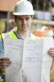 Bouwvakker On Building Site die Huisplannen bekijken royalty-vrije stock afbeelding