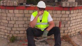 Bouwvakker die dichtbij de onvolledige bouw roken stock videobeelden