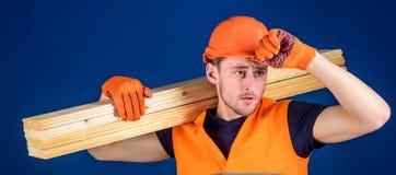 Bouwvakker die een houten plank op zijn schouder dragen Timmerman die bouwvakker, beschermende handschoenen en veiligheid dragen stock foto
