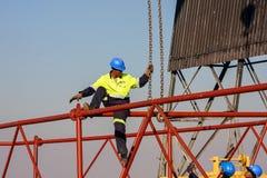 Bouwvakker die een ijzerstraal op een bouwterrein hijsen royalty-vrije stock afbeelding