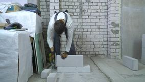 Bouwvakker die gelucht concreet blok malen bij bouwwerf stock footage