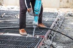 Bouwvakker die jackhammer het cement van de boorvloer gebruiken Stock Fotografie