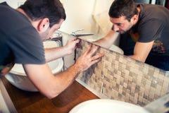 bouwvakker die keramische tegels, Tegelzetter leggen die ceramische muurtegel plaatsen in positie over kleefstof stock fotografie