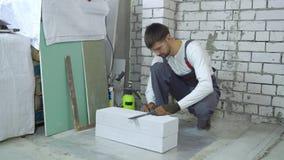 Bouwvakker die prijsverhoging op gelucht concreet blok doen bij bouwwerf stock footage