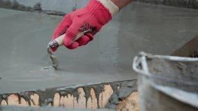 Bouwvakker die vers gegoten beton gladstrijken stock footage