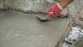 Bouwvakker die vers gegoten beton gladstrijken stock videobeelden