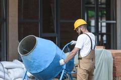 bouwvakker in bouwvakker en beschermende googles die met concrete mixer bij de bouw werken stock fotografie