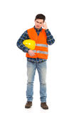 Bouwvakker in gele helm en oranje vest krassend hoofd. Stock Foto's