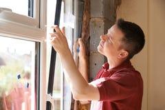 Bouwvakker Installing New Windows binnenshuis Stock Afbeeldingen