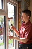 Bouwvakker Installing New Windows binnenshuis stock foto