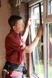 Bouwvakker Installing New Windows binnenshuis royalty-vrije stock afbeelding