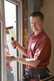 Bouwvakker Installing New Windows binnenshuis stock afbeelding