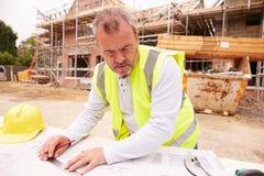 Bouwvakker Looking At Plans op Bouwterrein Royalty-vrije Stock Foto's