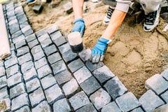 bouwvakker, manusje van alles dat de stenen van het keigraniet voor het creëren van het lopen weg gebruikt Terras of stoepdetails stock foto