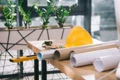bouwvakker, meetlint en blauwdrukken op lijst in modern stock foto's