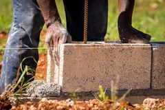 Bouwvakker/metselaar/metselaar die concreet blok op nat cement leggen stock fotografie