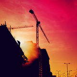 Bouwvakker op een gebouw in zonsondergang Stock Fotografie