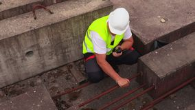 Bouwvakker op walkie-talkie dichtbij concrete blokken stock videobeelden