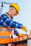 Bouwvakker in weerspiegelend vest en bouwvakker die bakstenen leggen royalty-vrije stock afbeeldingen