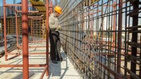 Bouwvakkers die die aan staalstaven worden gebruikt werken om concrete timelapse te versterken stock footage