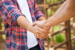Bouwvakkers die Handen schudden bij Plaats Stock Foto's