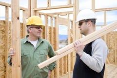 Bouwvakkers op de baan die een huis bouwt Stock Fotografie