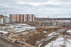 Bouwwerf, bouw van grote woon complex op de achtergrond van nieuwe huizen en bossen stock afbeelding