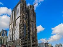 Bouwwerf, kraan en de grote bouw in aanbouw tegen blauwe bewolkte hemel stock afbeeldingen