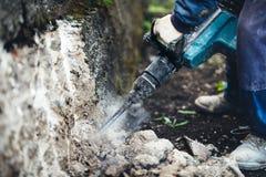 bouwwerf met arbeider die pneumatische jackhammer voor het vernietigen van een structurele muur gebruiken Stock Foto