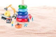 Bouwwerf met miniatuurarbeiders, stortplaatsvrachtwagen, graafwerktuig Stock Afbeelding