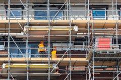 Bouwwerf nieuw flatgebouw met steiger en metselaararbeiders stock afbeelding