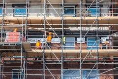 Bouwwerf nieuw flatgebouw met steiger en metselaararbeiders stock afbeeldingen